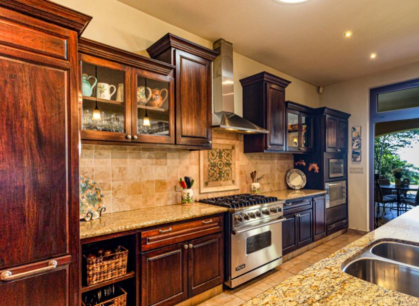 traditional kitchen with raised panel cabinets, a stone backsplash
